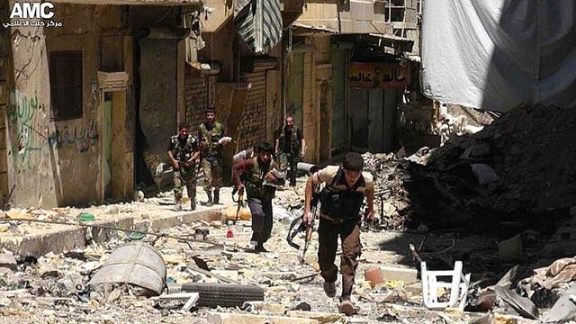 Syrische Rebellen laufen durch ein zerbombtes Wohngebiet.