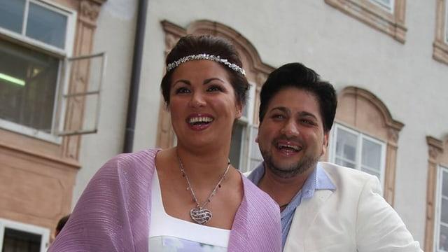 Anna Netrebko und Yusif Eyvazov strahlen. Sie trägt einen Kopfschmuck und ein lila Tuch über die Schultern.