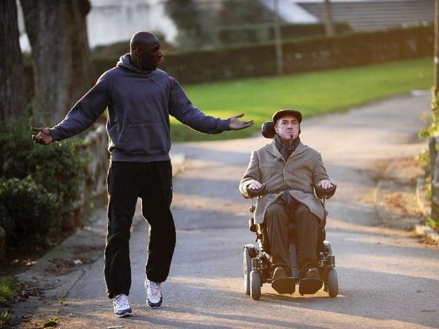 Ein Mann im Jogginganzug läuft neben einem Mann im Rollstuhl.