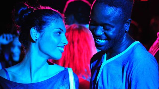Eine Frau und ein Mann in blauem Licht, beide lachen.