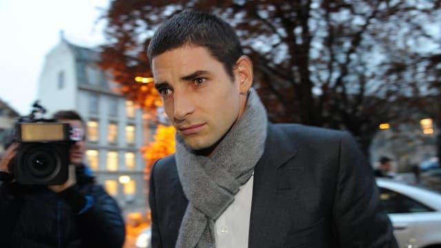 Ein junger Mann mit dickem Schal um den Hals ist im Visier von Medienleuten.