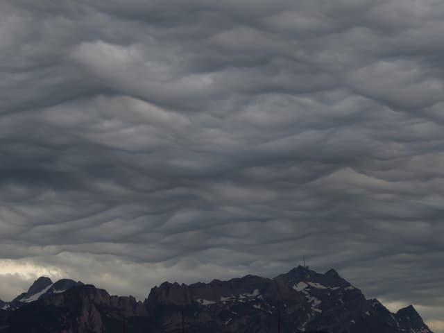 Dunkelgrauer Himmel. Die Wolkendecke erinnert an Wellen einer wilden See.