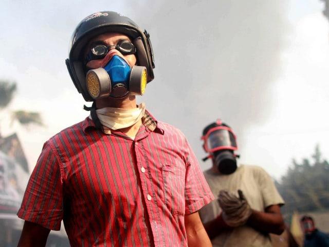Demonstranten tragen Gasmasken
