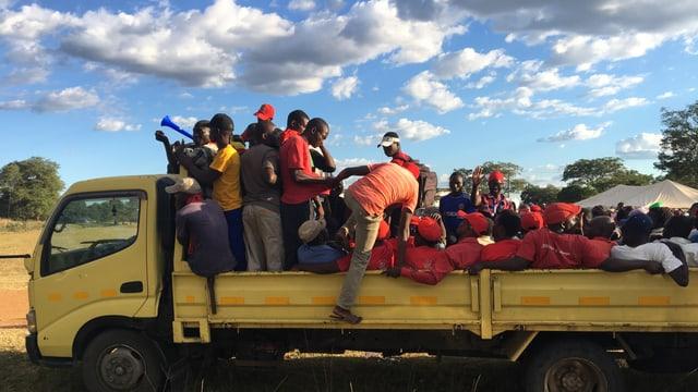 Junge Männer auf einem Lastwagen unter blauem Himmel.