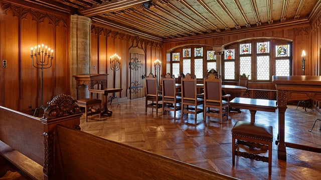 Ein alter hölzerner Raum mit edlen Stühlen um einen Holztisch.