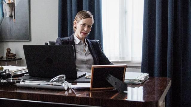 Eine Frau sitzt im Chefsessel, vor ihr ein Pult, darauf ein Laptop.