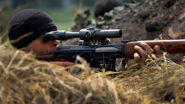 Ein Mann schaut durch das Fernrohr eines Gewehres.