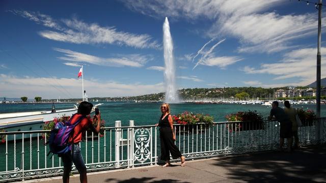 Ein Mann fotografiert eine Frau, sie steht am Genferseeufer mit dem Jet d'eau im Hintergrund.