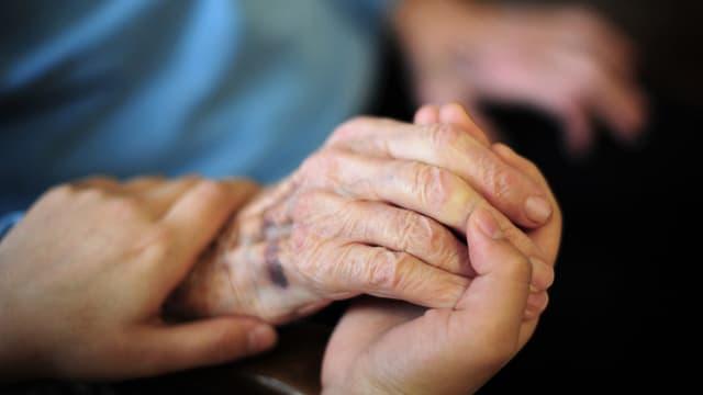 Symbolbild: Junge Hände halten eine alte Hand.