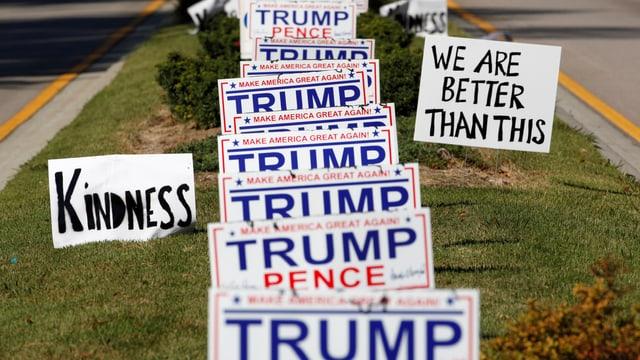 Trump/Pence-Schilder auf einer Grünfläche, Schilder «Kindness» und «We are better than this» daneben.