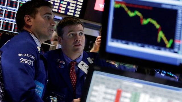 Zwei New Yorker Börsenhändler neben einem Bildschirm, der eine absteigende Kurve zeigt.