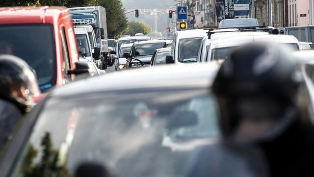 Mofas und Autos auf einer dicht befahrenen Strasse.