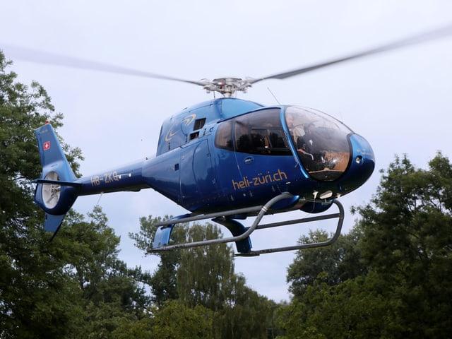 Blauer Helikopter in der Luft.