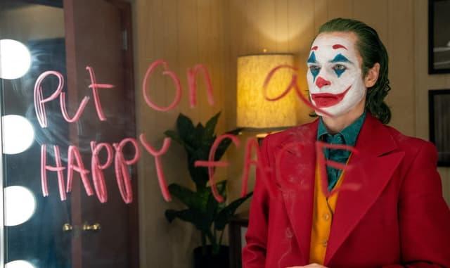 Ein Mann in rotem Anzug steht vor einem Spiegel, auf dem rot geschrieben steht: «Put on a happy face».