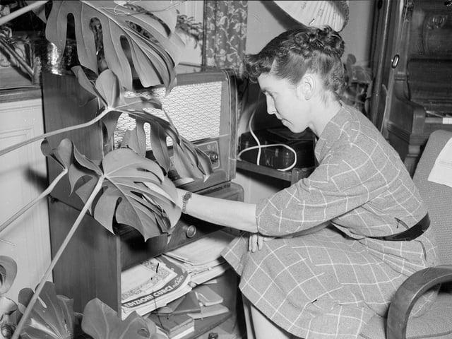 Historische Aufnahme in schwarz-weiss mit einer Frau, die vor einem grossen Radiogerät sitzt.