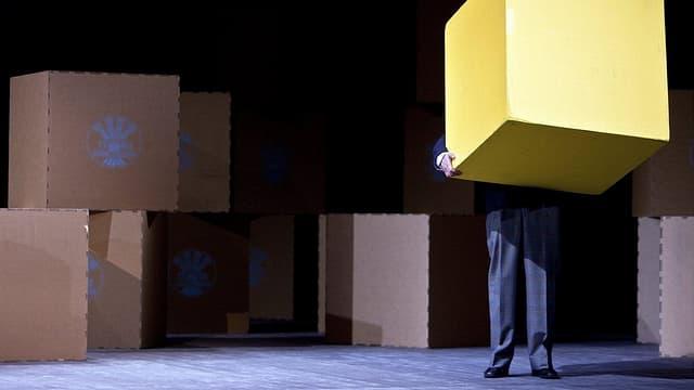 Ein Mann mit einer Box auf einer Bühne.