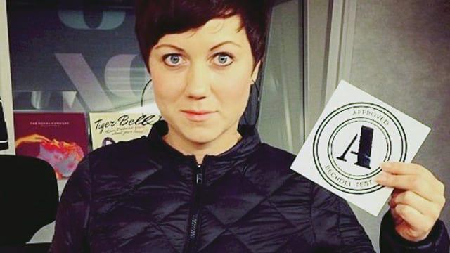 Eine Frau in dunkler Jacke hält einen weissen Zettel in der Hand, auf dem ein grosses A steht.