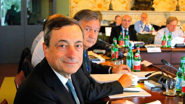 EZB-Präsident Mario Draghi lächelnd an einem Konferenztisch.