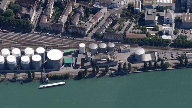 Die Tanklager von Esso von oben herab fotografiert, im Vordergrund der Rhein mit Schiff, dahinter Bahngleise und Häuser des Klybeckquartiers.