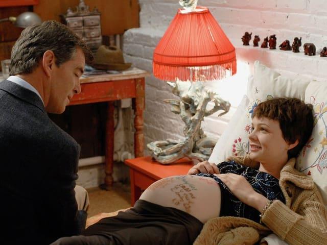 Pierce Brosnan als Allen Brewer sitzt am Bett der schwangeren Rose (Carey Mulligan), deren Bauch mit Filzstiften bemalt ist.