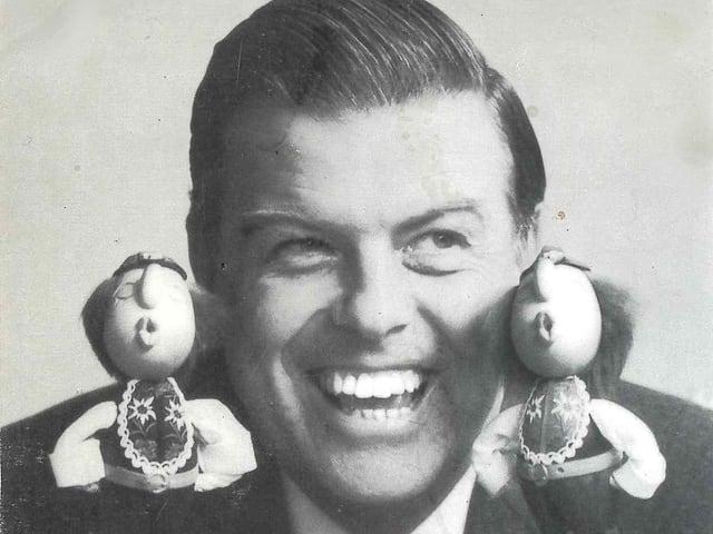 Schwarz-Weiss-Fotografie mit dem Kopf eines Mannes zwischen zwei pfeifenden Puppen.