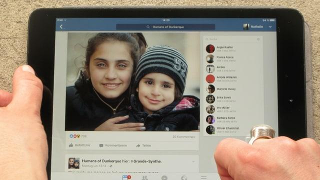Auf einem Tablet ist ein Foto zweier Kinder zu sehen, die in die Kamera lächeln.