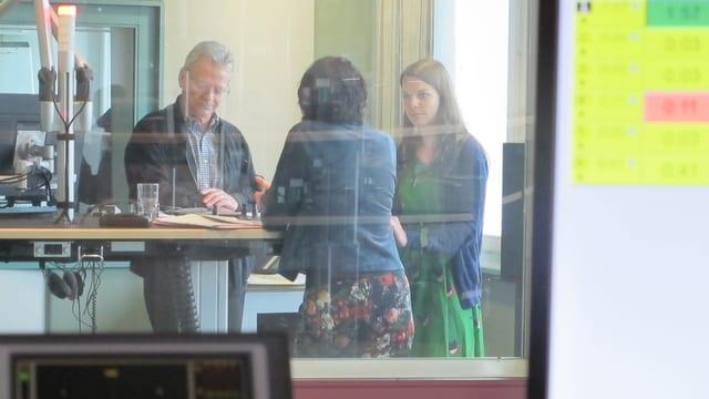 Drei Menschen sprechen in einem Radiostudio miteinander.