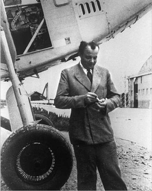 Schwarzweissbild: Saint-Exupéry im Anzug vor einem Flugzeug.