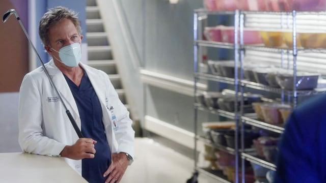 Einer der Ärzte der Serie mit einem Golfschläger in der Hand