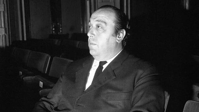 Der italienische Dirigent Nello Santi sitzt in einer Zuschauerreihe des Opernhauses und schaut auf die Bühne.