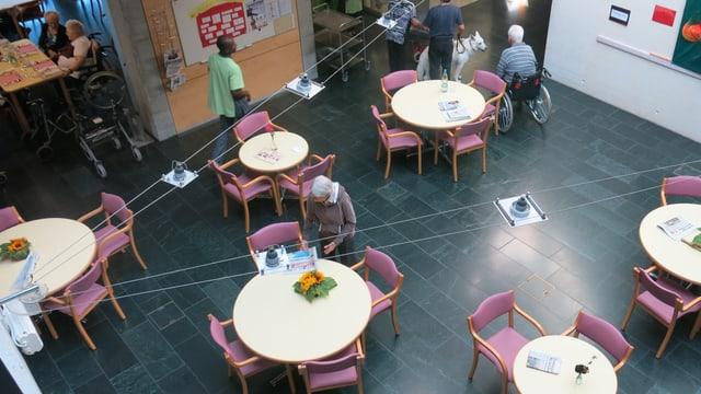 Die Caféteria im Heim mit Tischen und Stühlen, Bewohner sitzen dort.