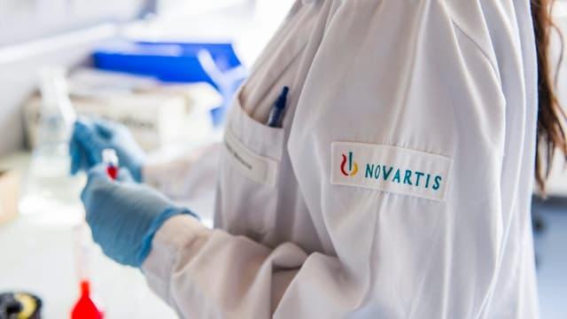 Frau mit Novartis-Kittel