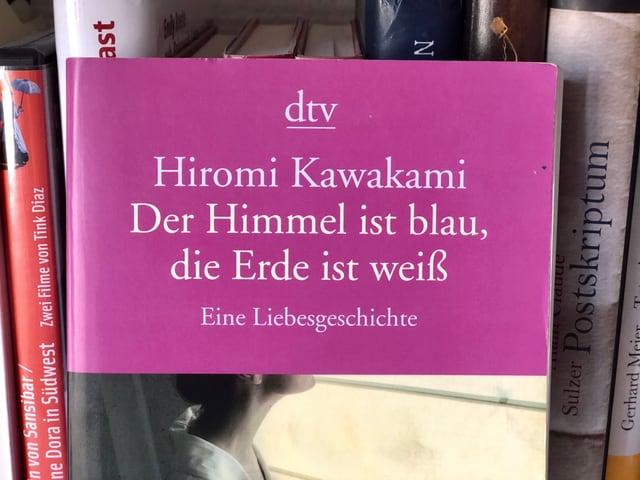 Hiromi Kawakami: «Der Himmel ist blau, die Erde ist weiss» auf einem Bücherregal stehend.