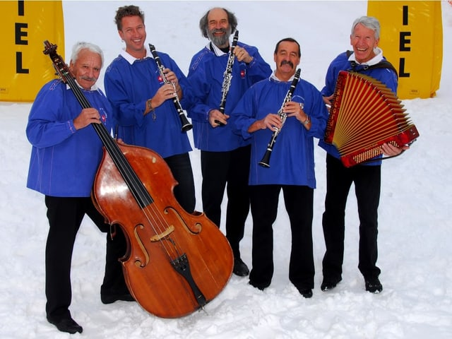 Engadiner Ländlerfründa mit Instrumenten. Blaue Sennenchutteli. Stehen in Kunstschnee.
