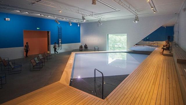 In einer grossen Halle ist ein Swimming Pool in der Grundform eines Hauses.