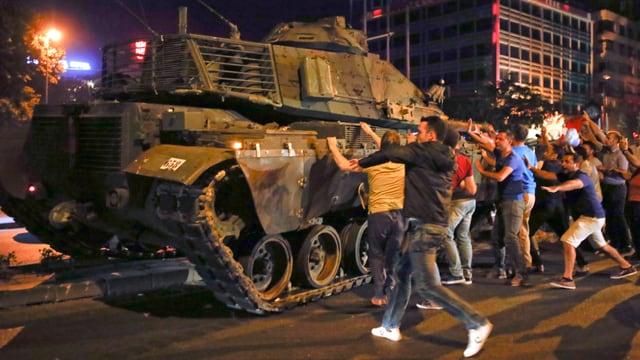 Menschenmenge versucht Panzer zu stoppen. Es ist dunkel.