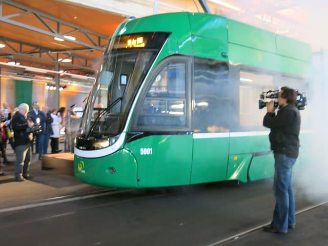 Buf des neuen Trams kommt aus dem künstlichen Rauch hervor, ein Kameramann filmt, im Hintergrund schauen viele zu.