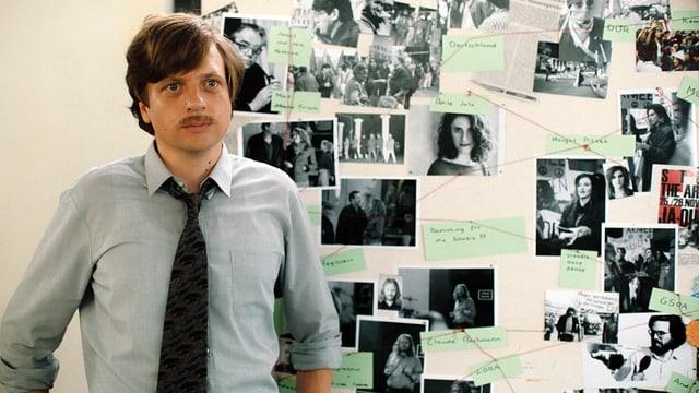 Ein Mann vor einer Wand mit Fotos.