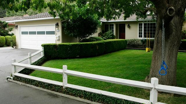 Garage, Rasen und Zaun eines Privatanwesens