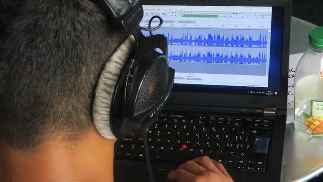 Ein Radioreporter sitzt vor einem Laptop und schneidet Töne zurecht.