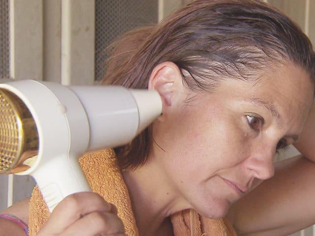 Eine Frau föhnt sich ihr Ohr.