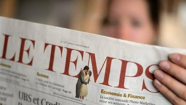 Eine Frau (unscharf im Hintergrund) liest die Zeitung Le Temps, die Titelseite gegen die Kamera gerichtet.