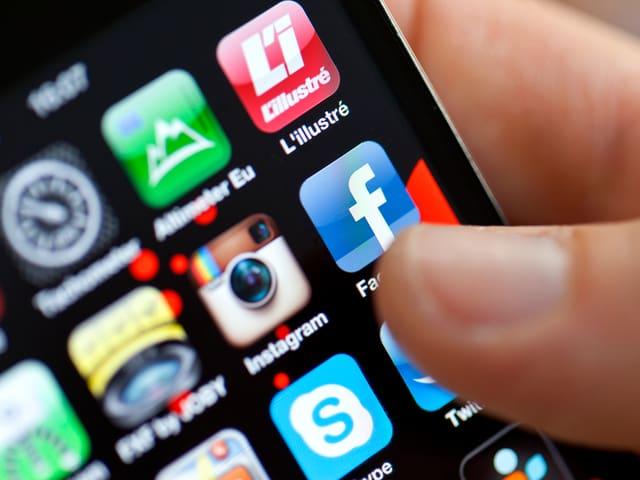Grossaufnahme eines Smartphone-Bildschirms, auf der ein Daumen das Symbol der Facebook-App wählt.