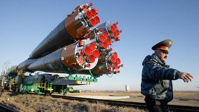 Symbolbild: Riesige, liegende Rakete, daneben ein russischer Funktionär mit grossem Hut.
