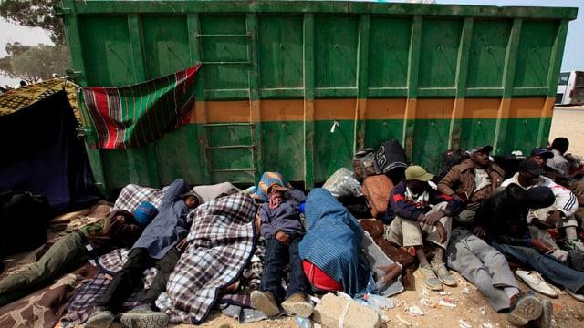 Flüchtlinge und Migranten liegen in einer Reihe an einer Mülltonne.