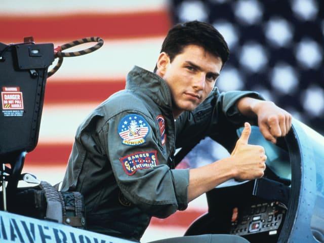 Tom Cruise in Fliegeruniform und hochgestrecktem Daumen im Cockpit eines Kampfjets
