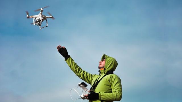 Ein Mann mit Fernsteuerung lästt Drohne starten.