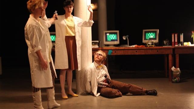 Ein Wissenschaftlerin bedroht eine andere, während ein Professor gefesselt am Boden sitzt.