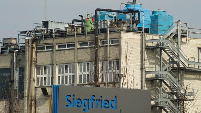 Fabrik mit Rohren etc., davor Schriftzug Siegfried