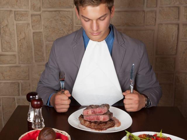 Mann mit einem Teller voller Fleisch